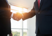 Cropped image of business people shaking hands, backlit