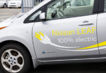 "Halifax, Nova Scotia, Canada - April 22, 2012: The side, left driver's door of a Nissan Leaf. On the side, decals are placed that display its operation of 100% electric. The ""Zero Emission"" badge is visible on lower portion of door. Other cars visible in background. The Nissan Leaf is a five-door hatchback electric car manufactured by Nissan and introduced in December 2010. The official range is 117 kilometres, and the combined fuel economy at 99 miles per gallon of the gasoline equivalent."