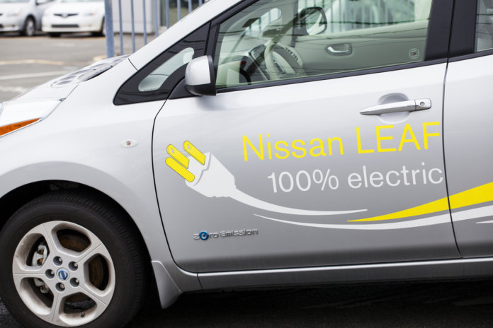 Halifax, Nova Scotia, Canada - April 22, 2012: The side, left driver's door of a Nissan Leaf. On the side, decals are placed that display its operation of 100% electric. The